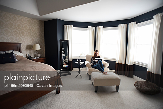 Woman sitting in chair on tablet in front of windows in a bedroom. - p1166m2090649 by Cavan Images