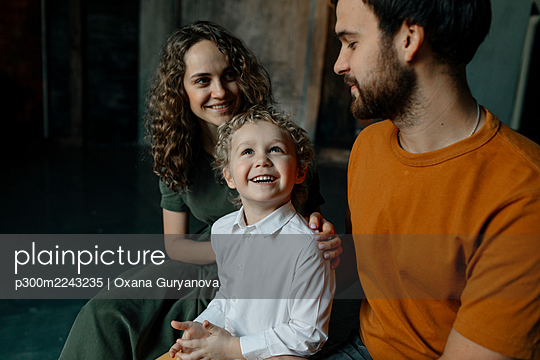 Son smiling while sitting by mother and father - p300m2243235 by Oxana Guryanova