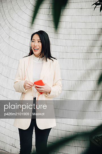 Smiling businesswoman holding smart phone and earphones against wall at office - p426m2101909 by Maskot