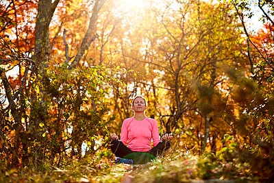 A woman meditates outdoors on a beautiful fall day. - p1166m2159535 by Cavan Images