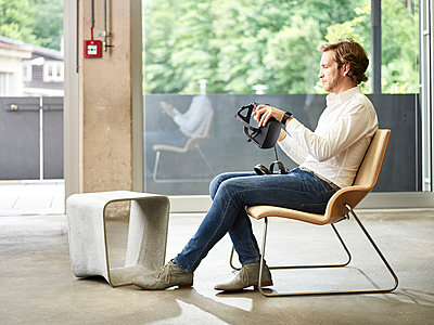 Man holding VR glasses sitting on chair - p300m1549918 by Christian Vorhofer