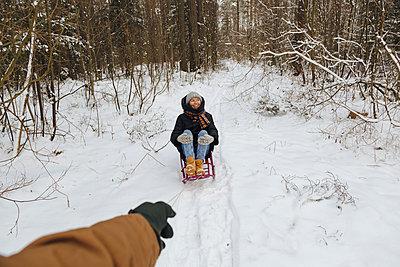 Man's hand pulls a woman on a sleigh, Leningrad region, Russia - p300m2166798 von Konstantin Trubavin