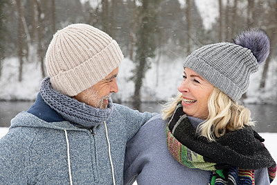 Happy senior couple in warm clothing looking at each other during winter - p300m2281822 by Frank van Delft