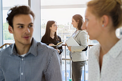 Germany, Bavaria, Munich, Male and female students talking in corridor - p924m2271296 by suedhang photography