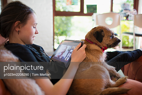 Girl with dog video chatting with friends on digital tablet screen - p1023m2208290 by Tom Merton