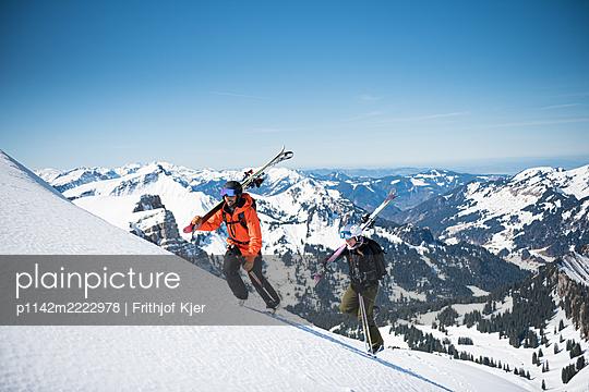 Zwei Skifahrer beim Aufstieg mit Skiern über der Schulter - p1142m2222978 von Frithjof Kjer