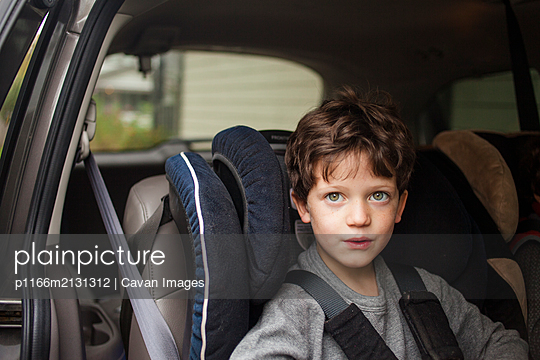 top half of a small child with direct gaze sitting in carseat in car - p1166m2131312 by Cavan Images