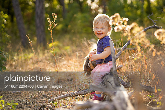 Small child laughing and sitting on a fallen tree - p1166m2294706 by Cavan Images