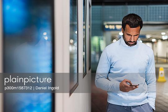 Businessman using smartphone at underground station - p300m1587312 von Daniel Ingold