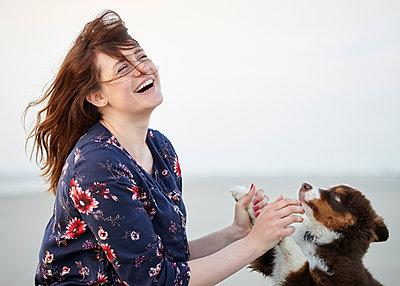 Frau spielt mit Hundewelpen - p1124m1223982 von Willing-Holtz