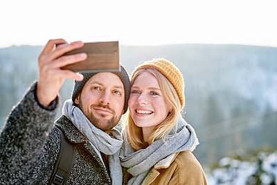 Young couple takes a selfie - p1124m1589347 by Willing-Holtz