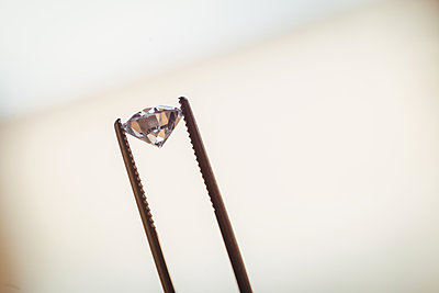 Close-up of diamond in forceps - p1315m1199381 by Wavebreak