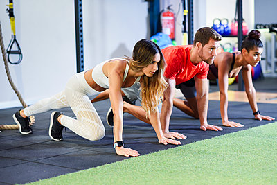 Young people exercising plank variations in a gym - p300m2060240 von Javier Sánchez Mingorance