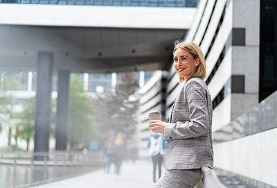 Smiling young businesswoman with takeaway coffee in the city - p300m2143484 by Daniel Ingold