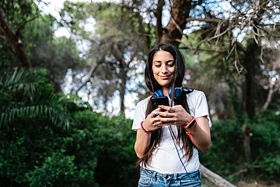 Woman with headset using smartphone in the woods - p300m2202572 by Ezequiel Giménez
