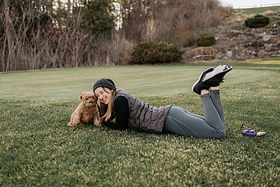 Smiling woman with poodle lying on grassy land in park - p300m2203102 by Sara Monika