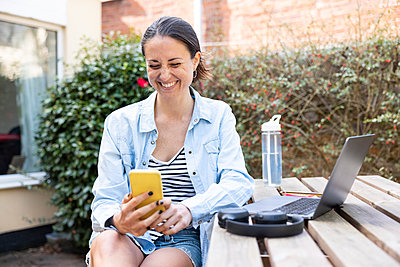 Smiling female professional using smart phone while sitting in garden - p300m2282882 by William Perugini