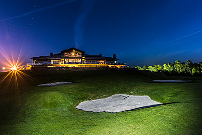 Golf course, illuminated building on background - p312m1471964 by Mikael Svensson
