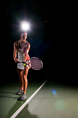 Woman playing tennis indoors - p42917785 by Mike Tittel
