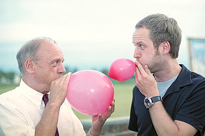 Father and son face to face blowing up balloon - p4901680 by Jan Mammey