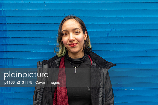 Mixed race woman looking to camera while standing in rain on blue wall - p1166m2131175 by Cavan Images
