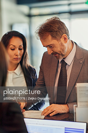 Business people checking in at reception desk in hotel