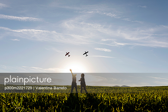 Playful brothers flying airplane toy while standing on grass in meadow - p300m2221729 by Valentina Barreto