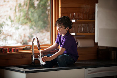 Boy filling water in glass while sitting at kitchen counter - p1166m1036454f by Cavan Images