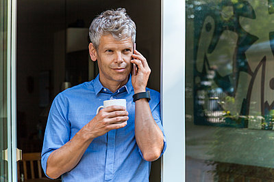 Portrait of mature man on the phone leaning agaich door case with coffee mug - p300m2030593 von Tom Chance