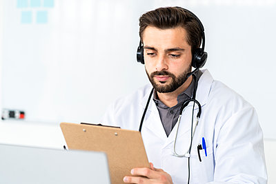 Handsome male doctor wearing headphone while reading report on clipboard in hospital - p300m2274649 by Giorgio Fochesato