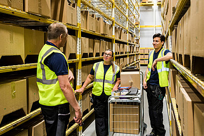 Multi-ethnic coworkers discussing while standing with cart on aisle amidst racks at distribution warehouse - p426m2018864 by Maskot