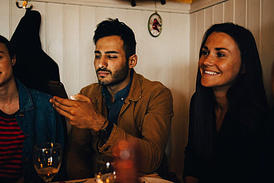 Young man using smart phone while sitting amidst female friends in restaurant during dinner party - p426m2046293 by Maskot