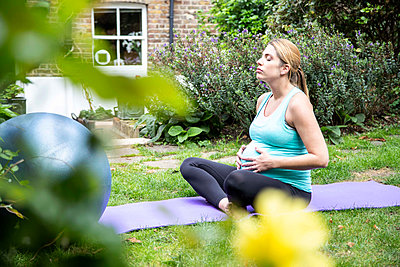 Pregnant mid adult woman practicing yoga meditation in garden - p429m2051098 by Grant Squibb