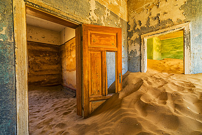 Sand in the rooms of a colourful and abandoned house; Kolmanskop, Namibia - p442m1086785 by Robert Postma