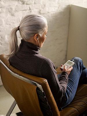 Aeltere Frau hoert Musik mit mp3-Player  - p6430235f von senior images RF