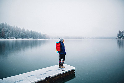 Hiker on snow covered pier looking at view of lake, Bass Lake, California, USA - p924m1180302 by Peter Amend