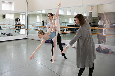 Instructor guiding ballet dancers practicing in dance studio - p1192m1403472 by Hero Images