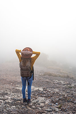 Woman with backback, standing on mountain, looking at view - p300m2078729 von VITTA GALLERY
