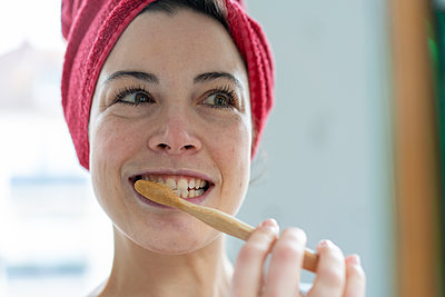 Portrait of woman with head wrapped in a towel brushing heer teeth with wooden toothbrush - p300m2170635 by Robijn Page