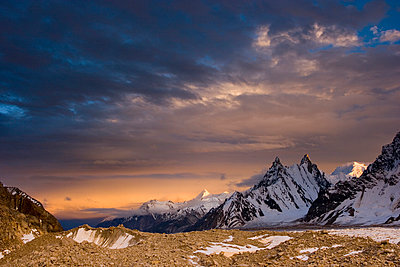 Alpenglow on clouds and mountains at sunset on the Biafo glacier in the Karakoram Himalaya of Pakistan - p343m1032085 by Bill Stevenson