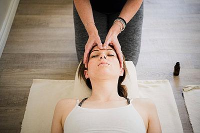 Woman enjoying head massage in yoga retreat - p429m2019541 by Hugh Whitaker