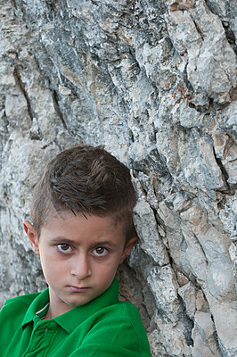 Young boy leaning against a rock  - p794m1119730 by Mohamad Itani