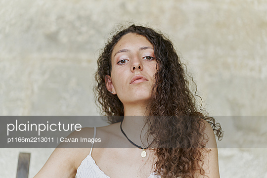Portrait of curly haired young woman with serious look - p1166m2213011 by Cavan Images