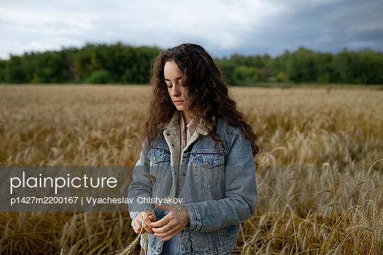 Russia, Omsk, Young woman standing in wheat field and holding wheat - p1427m2200167 by Vyacheslav Chistyakov