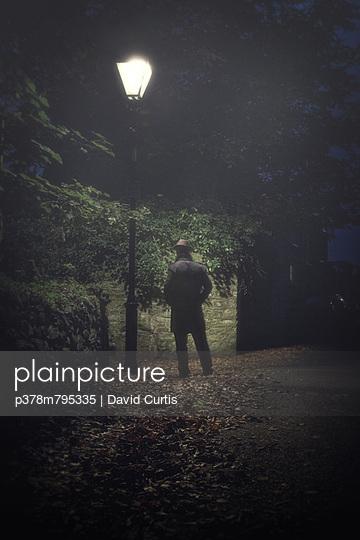 Man under lamp post - p378m795335 by David Curtis