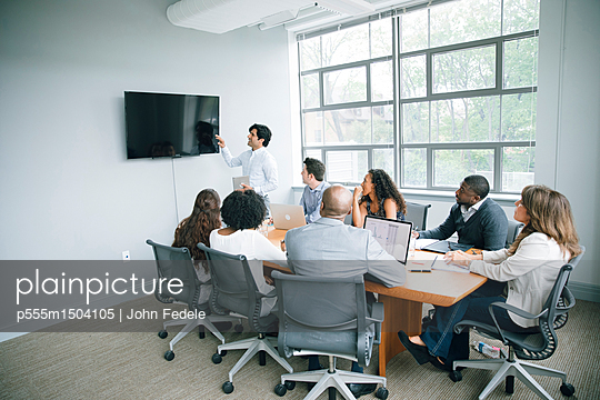 Businessman talking near visual screen in meeting - p555m1504105 by John Fedele