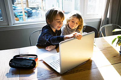 kids in morning light sitting at table doing remote school - p1166m2232747 by Cavan Images