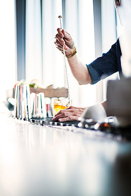 Cropped image of bartender stirring whisky in glass - p1264m1089200f by Astrakan