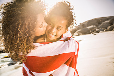 Happy mother and daughter wrapped in a towel on the beach - p300m2167092 by Floco Images