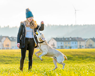 Cheerful woman playing with pet dog outdoors - p300m2257298 by Stefan Schurr